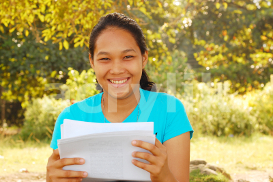 young smiling woman reading a document photo