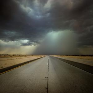 walking down a stormy desert road
