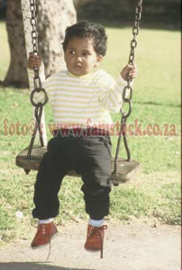 K6128- very non-smiling boy toddler on swing in bright sunlight | Photos and Images | Children